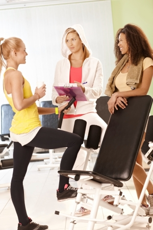 Fit girls talking to personal trainer at the gym. photo