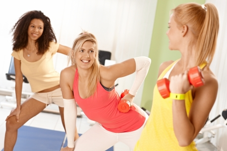Pretty girls exercising with dumbbells, smiling. photo