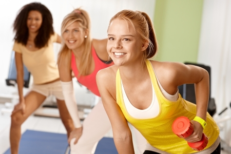 Fit girl exercising with dumbbells in group, smiling. photo