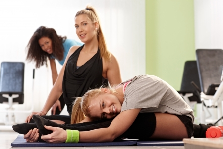 Flexible young girls exercising at the gym, smiling. photo