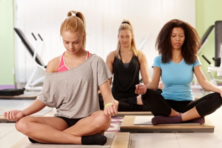 Young women meditating, relaxing at the gym eyes closed. photo