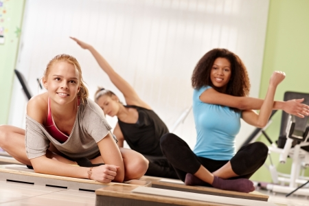 three women: Attractive women doing stretching exercises at the gym after workout.