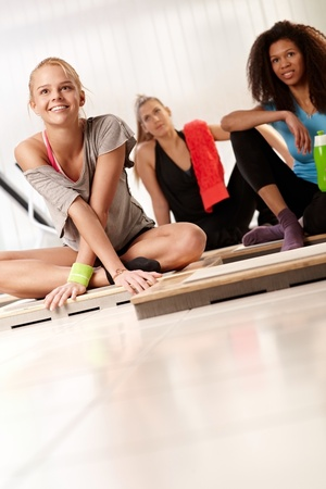 Young attractive females resting after workout at the gym. photo