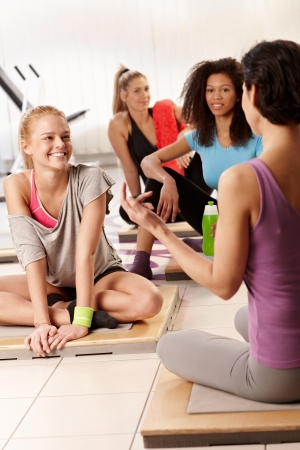 Young women and female instructor talking at the gym after workout. photo