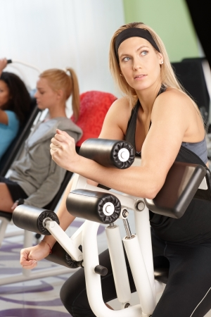 weight machine: Pretty young blond girl doing workout at the gym on weight machine.