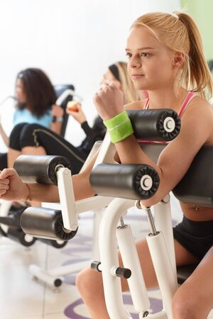 weight machine: Young girl working out on weight machine at the gym. Stock Photo