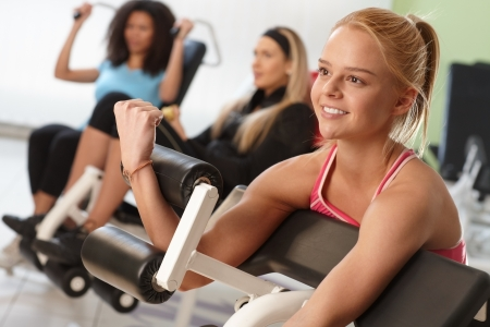weight machine: Pretty girl exercising on weight machine at the gym.