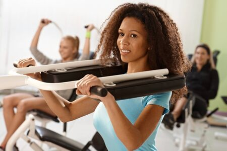 weight machine: Pretty ethnic girl exercising on weight machine at the gym, smiling. Stock Photo