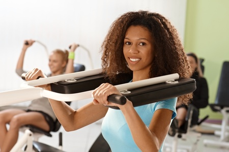 weight machine: Beautiful young afro woman training at gym using weight machine, smiling. Stock Photo