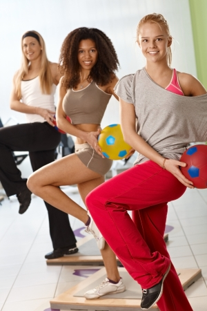 Happy young women exercising with ball at the gym. photo