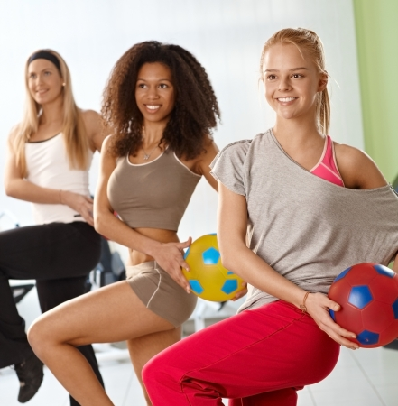 Pretty young girls exercising with ball at the gym, smiling. photo
