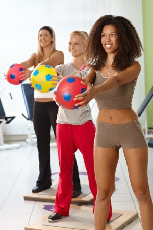 Pretty females exercising with ball at the gym, smiling. photo