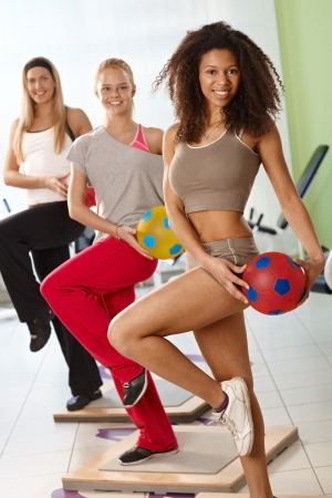 Three women exercising with ball at the gym, smiling. Stock Photo - 14746204