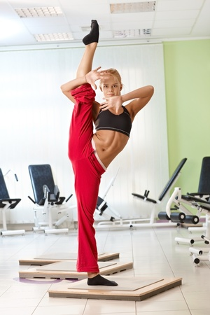 Pretty blond female gymnast posing. Standing on one leg, lifting the other. Stock Photo
