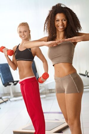 Pretty girls exercising at the gym, smiling. Stock Photo - 14746210