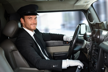 Handsome smiling chauffeur driving limousine. photo