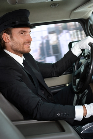 chauffeur: Elegant chauffeur driving luxurious car, smiling. Stock Photo