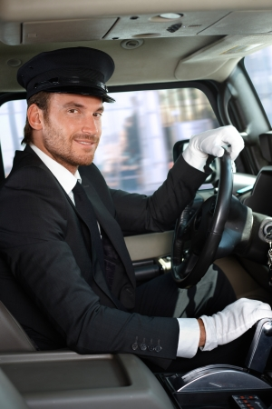 chauffeur: Elegant young chauffeur driving limousine, smiling. Stock Photo