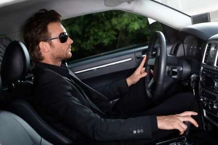 Elegant man driving a luxury car.