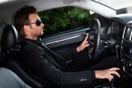 offish: Elegant man driving a luxury car.