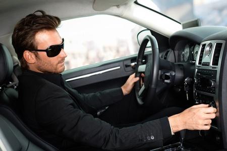 Man in black sitting in luxury car. Stock Photo