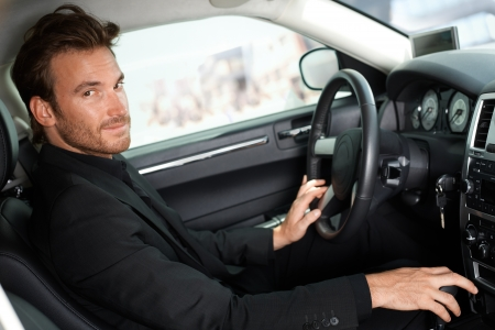 Handsome young man sitting in luxury car, looking at camera.