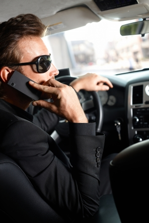 offish: Young man sitting in limousine, talking on cellphone.
