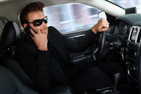 Elegant young man in black sitting in limousine, talking on mobile phone. photo