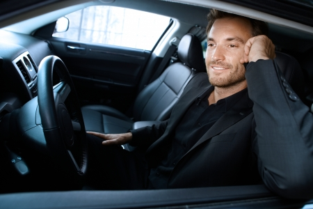 Handsome man sitting in limousine, talking on cellphone, smiling. photo