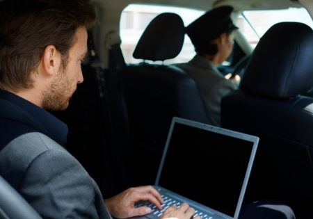 chauffeur: Young man in limousine working on laptop computer.