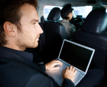 Young man working on laptop computer, sitting in limousine, chauffeur driving. photo