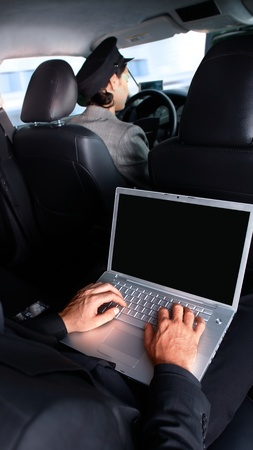 Businessman working on laptop computer, sitting in limousine. photo