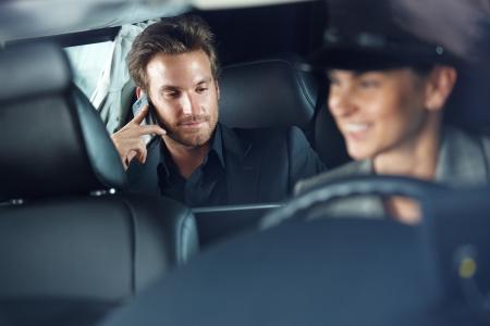 Businessman using cellphone in limousine, female chauffeur driving.