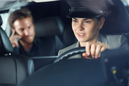 Female chauffeur driving a limousine, businessman in background. photo