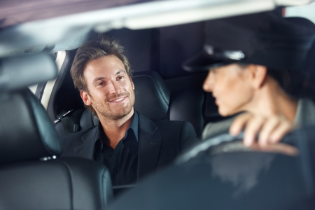 chauffeur: Handsome man sitting in luxury car, female chauffeur driving.