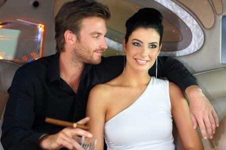 amigos abrazandose: Retrato de la joven pareja elegante sentado en limusina, sonriendo.