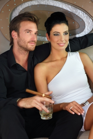 man smoking: Attractive young couple of high society drinking, smoking cigar, smiling.