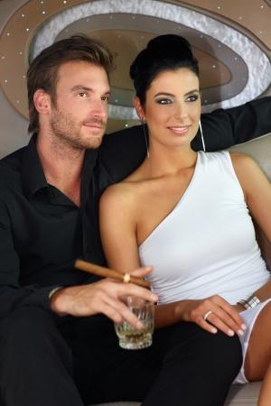 cigar smoking man: Pareja joven y atractiva de la bebida de la alta sociedad, fumar cigarros, sonriendo.