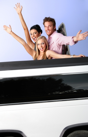 Attractive young people having fun in limousine, waving. photo