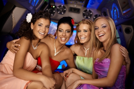Beautiful young girls having party in limousine, smiling. photo