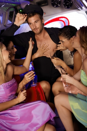 chauffeur: Hot hen party in limousine with beautiful girls and chauffeur boy. Stock Photo