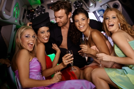 hen party: Sexy girls having fun in limousine with handsome man at bachelorette party. Stock Photo