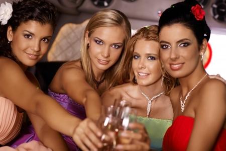 socializando: Atractivas chicas elegantes celebrando con champán, sonriendo.