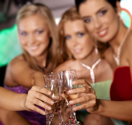 jovenes tomando alcohol: Tintineo de vasos, celebrando con champ�n. Foto de archivo
