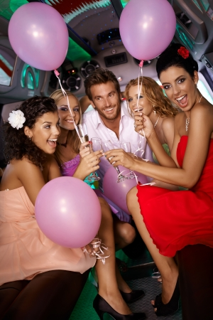 Beautiful young girls having party fun in limousine with handsome man. photo