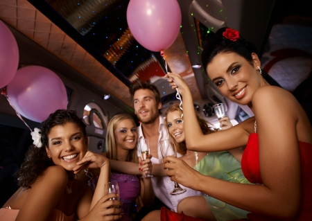 party balloons: Hen party in limousine with attractive young people. Stock Photo
