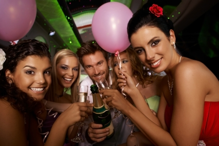 hen party: Bachelorette party in limousine with attractive young people, having fun.