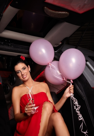 Attractive female in red cocktail dress smiling, sitting in limousine door. photo