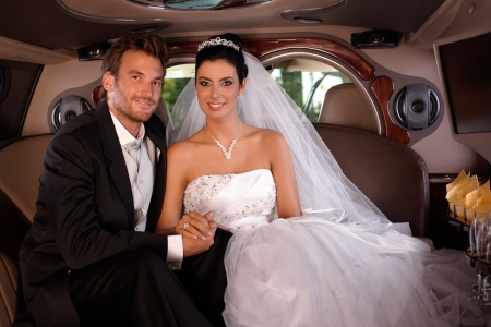 Bride and groom sitting happily in limo on wedding-day. photo