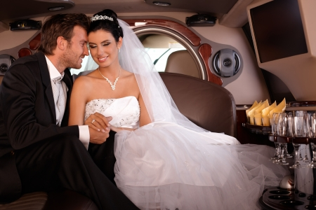 wedding portrait: Beautiful young couple sitting in limousine on wedding-day, smiling.